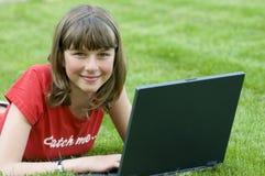 Adolescente que trabaja en el ordenador en la hierba Foto de archivo libre de regalías