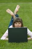 Adolescente que trabaja en el ordenador en la hierba Imagen de archivo libre de regalías