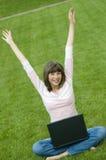 Adolescente que trabaja en el ordenador en la hierba Imagen de archivo