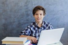 Adolescente que trabaja en el ordenador portátil en casa Fotografía de archivo libre de regalías