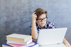 Adolescente que trabaja en el ordenador portátil en casa Imagen de archivo libre de regalías