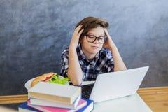 Adolescente que trabaja en el ordenador portátil en casa Imágenes de archivo libres de regalías