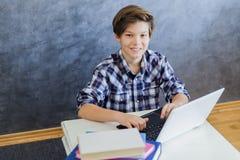 Adolescente que trabaja en el ordenador portátil en casa Fotografía de archivo