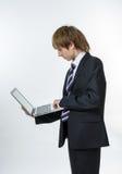 Adolescente que trabaja en la computadora portátil blanca Imagen de archivo