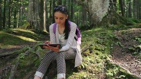 Adolescente que trabaja en la PC digital de la tableta almacen de metraje de vídeo