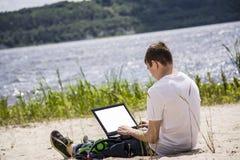 Adolescente que trabaja para un ordenador portátil en la playa Imagen de archivo libre de regalías