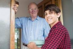 Adolescente que trae la comida para el vecino masculino mayor Fotografía de archivo