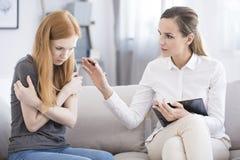 Adolescente que tranquiliza del psicoterapeuta con problema Imágenes de archivo libres de regalías