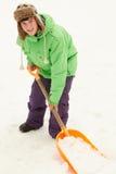 Adolescente que traspala nieve del camino Foto de archivo libre de regalías