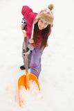Adolescente que traspala nieve del camino Foto de archivo