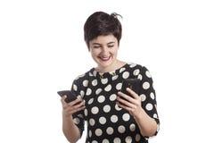 Adolescente que usa dos smartphones Fotos de archivo