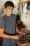 Adolescente que usa el banco de trabajo en garaje Fotografía de archivo