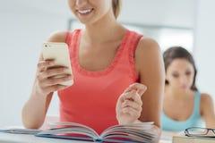 Adolescente que usa el móvil en la sala de clase Fotografía de archivo