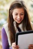 Adolescente que usa el ordenador de la tablilla al aire libre Foto de archivo