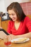 Adolescente que usa el ordenador de la tablilla mientras que come Imagen de archivo libre de regalías