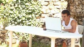 Adolescente que usa el ordenador en tiempo de verano del jardín almacen de video