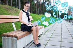 Adolescente que usa el ordenador portátil con diversos usos en parque o Foto de archivo libre de regalías