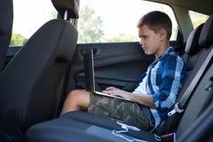 Adolescente que usa el ordenador portátil en el asiento trasero del coche Imágenes de archivo libres de regalías