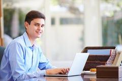 Adolescente que usa el ordenador portátil en el escritorio en casa Imagen de archivo libre de regalías