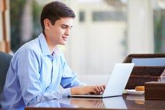 Adolescente que usa el ordenador portátil en el escritorio en casa Fotos de archivo