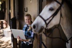 Adolescente que usa el ordenador portátil en el establo Fotos de archivo libres de regalías