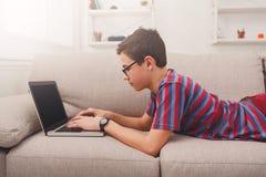 Adolescente que usa el ordenador portátil en el sofá en casa Fotos de archivo libres de regalías
