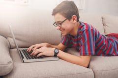 Adolescente que usa el ordenador portátil en el sofá en casa Imágenes de archivo libres de regalías