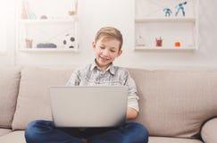 Adolescente que usa el ordenador portátil en el sofá en casa Fotos de archivo