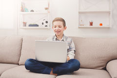 Adolescente que usa el ordenador portátil en el sofá en casa Fotografía de archivo libre de regalías