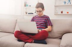 Adolescente que usa el ordenador portátil en el sofá en casa Imagenes de archivo