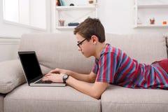 Adolescente que usa el ordenador portátil en el sofá en casa Imagen de archivo