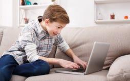 Adolescente que usa el ordenador portátil en el sofá en casa Imagen de archivo libre de regalías