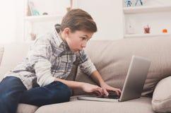 Adolescente que usa el ordenador portátil en el sofá en casa Fotografía de archivo
