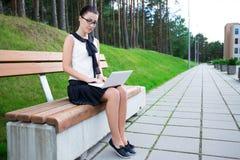 Adolescente que usa el ordenador portátil en parque o campus Foto de archivo libre de regalías