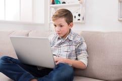 Adolescente que usa el ordenador portátil en el sofá en casa Foto de archivo