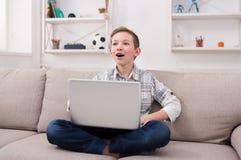 Adolescente que usa el ordenador portátil en el sofá en casa Foto de archivo libre de regalías