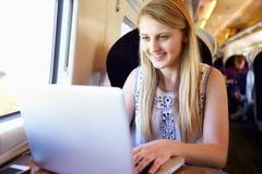Adolescente que usa el ordenador portátil en viaje de tren Imagen de archivo libre de regalías