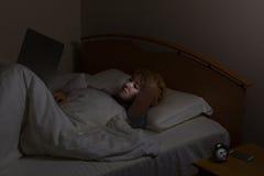 Adolescente que usa el ordenador portátil mientras que en cama Imagenes de archivo