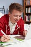 Adolescente que usa el ordenador portátil para la preparación en dormitorio Imagen de archivo libre de regalías
