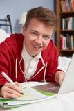 Adolescente que usa el ordenador portátil para la preparación en dormitorio Imagen de archivo