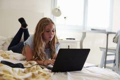 Adolescente que usa el ordenador portátil que miente en su cama Imagen de archivo libre de regalías
