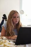 Adolescente que usa el ordenador portátil que miente en su cama, vertical Fotografía de archivo