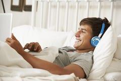Adolescente que usa el ordenador portátil y los auriculares en cama en casa Imagenes de archivo