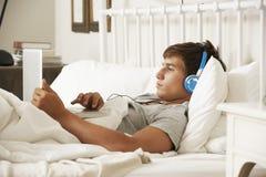 Adolescente que usa el ordenador portátil y los auriculares en cama en casa Fotografía de archivo