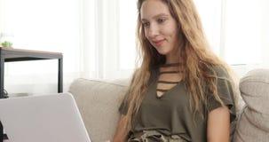 Adolescente que usa el ordenador port?til en el sof? metrajes
