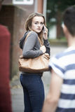 Adolescente que usa el teléfono como ella siente intimidada en hogar del paseo Imagenes de archivo