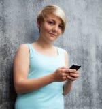 Adolescente que usa el teléfono elegante Imágenes de archivo libres de regalías