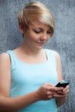 Adolescente que usa el teléfono elegante Imagen de archivo