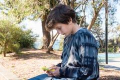 Adolescente que usa el teléfono elegante al aire libre Imagen de archivo libre de regalías