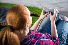 Adolescente que usa el teléfono elegante en parque Fotos de archivo